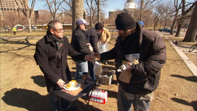 The Rev. Jerry Herships (left) offers communion bread to a homeless man in Denver. A UMNS photo by Carey Moots. ; A UMNS photo by Carey Moots
