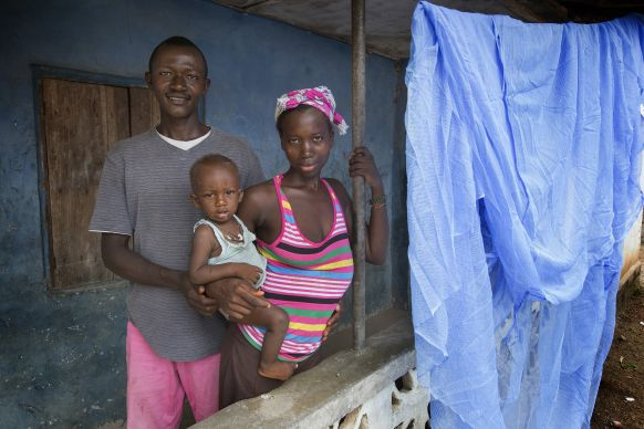 Abdul and Maseray Koroma stand with their daughter, Kelvin, 9 months, beside the new insecticide-treated mosquito net they received from the Imagine No Malaria campaign. The ministry of the United Methodist Church is providing some 350,000 nets as part of an integrated health campaign during the national Maternal and Child Health Week. Health officials recommend hanging the nets outdoors overnight before using them inside to allow the insecticide to dissipate some. Photo by Mike DuBose, UMNS