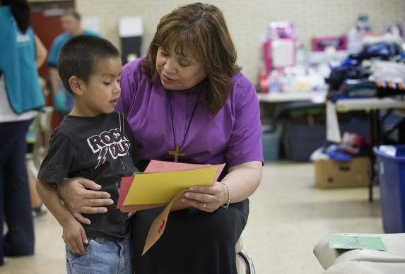 United Methodist Bishop Minerva Carcaño (right) shares letters of encouragement with Regino Enrique at the immigrant welcome center at Sacred Heart Catholic Church in McAllen, Texas. The 5-year-old and his mother, Macaria, who did not share their last names, arrived from Guatemala after a month-long journey. Photo by Mike DuBose, UMNS..Editors Note: Regino Enrique is NOT an  unaccompanied minor. He traveled from Guatemala with his mother, Macaria.