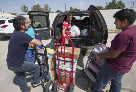 Volunteers from the Aposento Alto (Upper Room) Methodist Church in Nuevo Laredo, Mexico, help unload relief supplies for immigrants at the Holding Institute in Laredo, Texas. From left are: Edward Solis, youth member of Aposento Alto; Terry Schonert, United Methodist Women; the Rev. Jacer Davila, pastor at Aposento Alto; and Mario Ruiz, youth president at Aposento Alto. Schonert regularly brings supplies the the welcome center at the Holding Institute. Photo by Mike DuBose, UMNS.