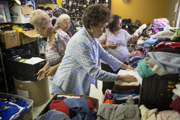 Elizabeth Jimenez (foreground) helps sort donated clothing for recent immigrants from Central America in the welcome center at the Holding Institute in Laredo, Texas. Jimenez was a student in the boarding school at Holding, a United Methodist Women National Mission Institution. She is flanked by, from left: Rosa Maria Narvaez, Lydia Mejorado and Elva Guzman. The volunteers are United Methodist Women from La Trinidad United Methodist Church in Laredo. Photo by Mike DuBose, UMNS.