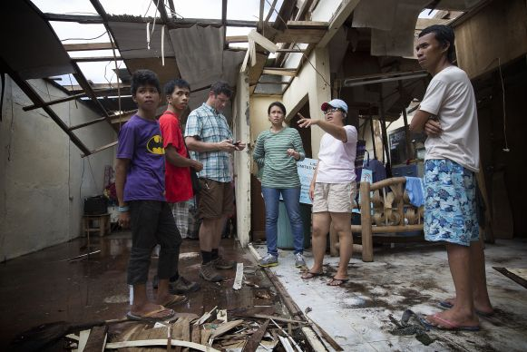 Pastor Iris Picardal Terana (second from right) describes damage from Typhoon Haiyan at Light and Life United Methodist Church in Tacloban, Philippines for a visiting technology team from United Methodist Communications and Inveneo. From left are: church member Ronell de Juan; Ernani Celzo, working with UMCom; Clark Ritchie of Inveneo, April Gonzaga-Mercado, working with UMCom; Terana; and her husband Jhonril Terana. Photo by Mike DuBose, UMNS