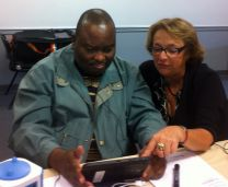 The Rev. Damião Elias, a member of the Commission on General Conference, and interpreter Isaura Arez practice using a Bible app on a tablet. Elias, who is from Mozambique, is among nine commission members who received training from United Methodist Communications and will participate in a pilot project using the tablets. The hope is that the tools will help delegates, especially from Africa and the Philippines, in preparing for General Conference. Photo by Heather Hahn, UMNS