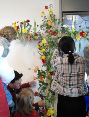 Easter service visitors at Neuenhain United Methodist Church near Frankfurt, Germany transform a cross of wire mesh to one with fresh flowers to convey the