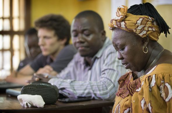 Beatrice Gbanga (right) leads a prayer at the opening of a panel discussion at the United Methodist Church's Mercy Hospital in Bo, Sierra Leone, to help prepare health care workers for a possible outbreak of the Ebola virus. Gbanga, medical and health coordinator for the church's Sierra Leone Annual Conference, is joined by, from right: research scientist Rashid Ansumana, Jesse Bonwitt, who is preparing a masters thesis on Lassa fever and hospital business manager Roland Stevens. Photo by Mike DuBose, UMNS