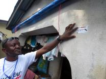 Volunteers place stickers on buildings they visit while sharing information about Ebola. Friday, Sept. 19, was day one of a three day lockdown in Sierra Leone. Photo by Phileas Jusu.