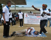 "Young adults from the Sierra Leone Annual Conference reenact skits relating the Ebola virus prevention and treatment in effort to educate. Their efforts are target people who cannot read or write or have access to radio and new media. The person in the head wrap represents an herbalist who works in ""African magic."" In the skit, the young man affected with Ebola is brought to the herbalist but dies. The brother who was exposed to the Ebola patient survives as he reports for (medical) treatment early. The message is that no superstitious power can cure Ebola; contact with an infected person can lead to infection; and there is a better chance for survival if one reports it early. The training was developed by the Youth and Young Adult Ministries. Photo by Phileas Jusu, UMNS"