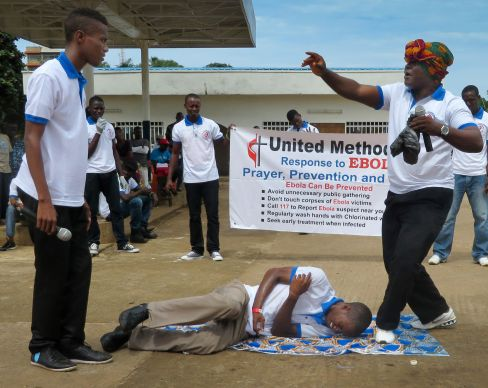 """Young adults from the Sierra Leone Annual Conference reenact skits relating to Ebola virus prevention and treatment in effort to educate. Their efforts are target people who cannot read or write or have access to radio and new media. The person in the head wrap represents an herbalist who works in """"African magic."""" In the skit, the young man affected with Ebola is brought to the herbalist but dies. The brother who was exposed to the Ebola patient survives as he reports for (medical) treatment early. The message is that no superstitious power can cure Ebola; contact with an infected person can lead to infection; and there is a better chance for survival if one reports it early. The training was developed by the Youth and Young Adult Ministries. Photo by Phileas Jusu, UMNS"""