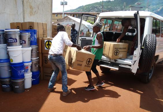 Volunteers unloading relief items at Braima Attouga Stadium in eastern Freetown. Photo by Phileas Jusu, UMNS