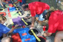 Volunteers at Hands Across the City paint concrete play area of children's playground.;