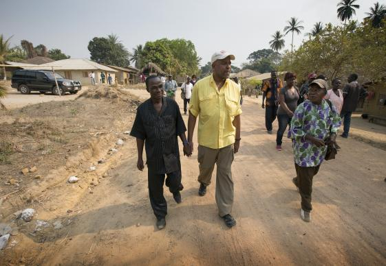 The Rev. Gary Henderson (center) walks hand in hand with Harry Kombar during a visit to Fulawahun village near Bo, Sierra Leone. Henderson heads the United Methodist Church's Imagine No Malaria campaign and Kombar is headmaster of the Fulawahun United Methodist Primary School. At right is United Methodist Pastor Moses Sandy. Several villages in the Bo district will receive new, insecticide-treated mosquito nets in the first planned redistribution to replace nets given in 2010. Photo by Mike DuBose, UMNS