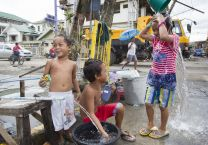Children bathe in water from an open pipe following Typhoon Haiyan in Tacloban, Philippines. A UMNS photo by Mike DuBose.