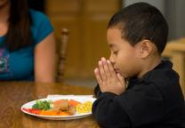 Geoffrey Booker, 6, prays before mealtime at his home in Brentwood, Tenn. File photo by Mike DuBose, United Methodist Communications.