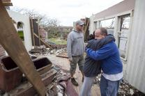 Laura Gage (center) hugs Joe Royer while helping sort through the wreckage of his home in Joplin, Mo.,following the deadly tornado. At left is Kevin Kaufhardt. A UMNS photo  by Mike DuBose.; A UMNS photo by Mike DuBose