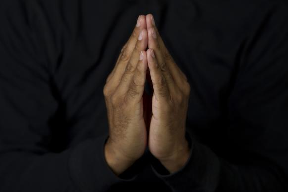 Hands are folded in prayer. Photo by Mike DuBose, United Methodist Communications.