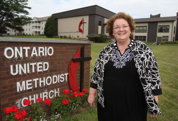 The Rev. Peggy L. Welch, pastor of Ontario United Methodist Church in Ontario, Ohio stands in the front of the church complex. The cross and flame appears both on the church and the sign. Photo by Kathleen Barry, United Methodist Communications