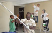 "Haitian volunteers Felicien Asthene (center) and Joliere Lafortune (left) help United Methodist volunteers the Rev. Kyewoon Choi (left background) of Embury United Methodist Church in Little Silver, N.J., and the Rev. Darleen Schott of First United Methodist Church in Washington, N.J., paint the home of ""Sister Paulette"" Holly at the Methodist Children's Home orphanage in Port-au-Prince, Haiti. A UMNS photo by Mike DuBose. Accompanies UMNS story #11. 1/12/11.; A UMNS photo by Mike DuBose"