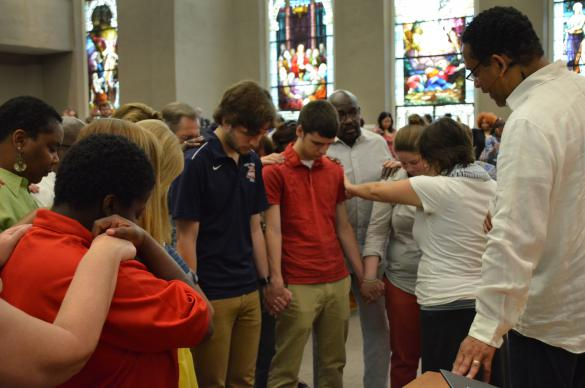 The Rev. Stephen Handy prays with the staff of the YouthWorks mission camp at McKendree United Methodist Church in Nashville, Tenn. Photo courtesy of McKendree United Methodist Church.