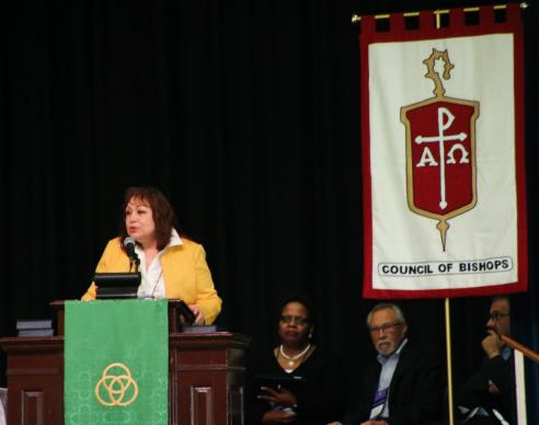 Bishop Minerva Carcaño, chair of the COB Immigration Task Force, presents the report and statement about immigration caravans during the plenary session at Epworth By the Sea on St. Simon's Island in Georgia.