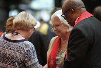 Bishop W. Earl Bledsoe prays with a small group at General Conference 2016 in this file photo.