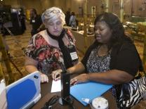 Shelia Mayfield (right) of United Methodist Communications demonstrates an overhead projector for Cindy Campbell in the Innovation Fair display at the 2014 Game Changers Summit in Nashville, Tennessee.