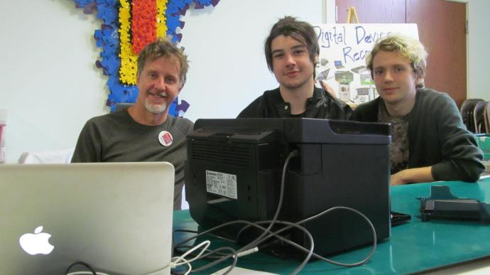 Computer professional Alan Macaluso and New Paltz High School seniors Luke McConnell (center) and Will Brasington staff the digital repair table.
