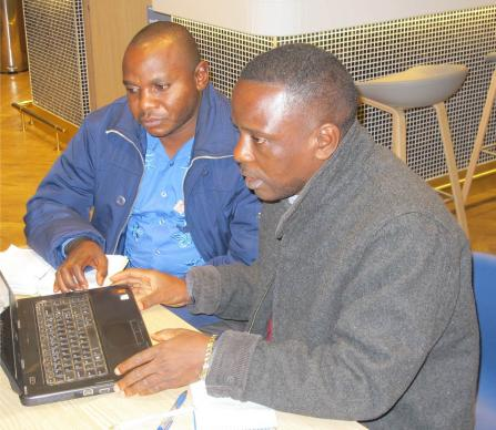 Dr. Alexis Ngoy Kasole Maloba (left), United Methodist Church health coordinator in Democratic Republic of Congo, and Dr. Philippe Okonda Akasa, health coordinator for East Congo, examine data on malaria at the recent Alliance for Malaria Prevention Conference in Geneva.