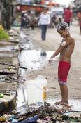 A child bathes in water from an open pipe following Typhoon Haiyan in Tacloban, Philippines. Natural and humanitarian disasters often raise questions of why there is suffering.