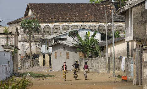 Women walk past the crumbling French colonial architecture in Grand Bassam, Côte d'Ivoire, the birthplace of Methodism in the West African country. UMNS photos by Mike DuBose.