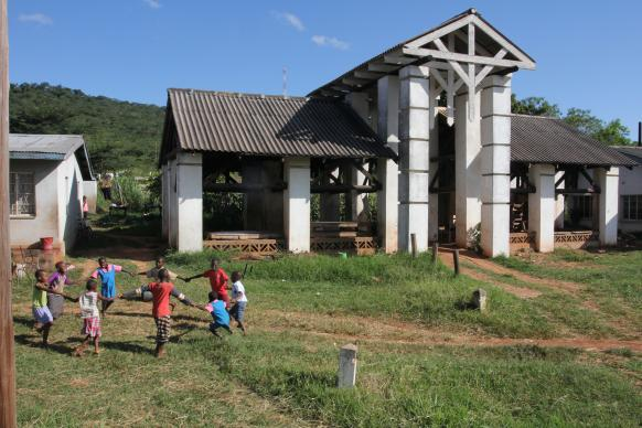 Children play a game in the farm area of Africa University in 2013.  The building in the background was the original building where students gathered for breaks and outdoor dining in 1992.