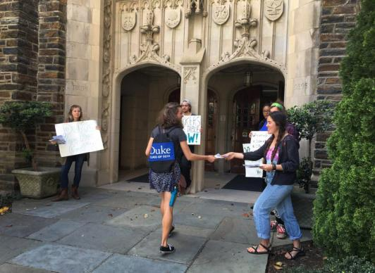 Students await visitors with signs outside Page Auditorium on the campus of Duke University.