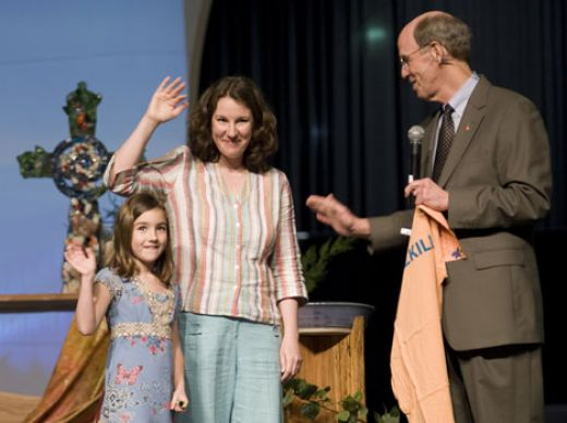 Seven-year-old Katherine Commale and her mother, Lynda, wave to delegates at the 2008 United Methodist General Conference after giving Bishop John Hopkins a Nothing But Nets T-shirt.