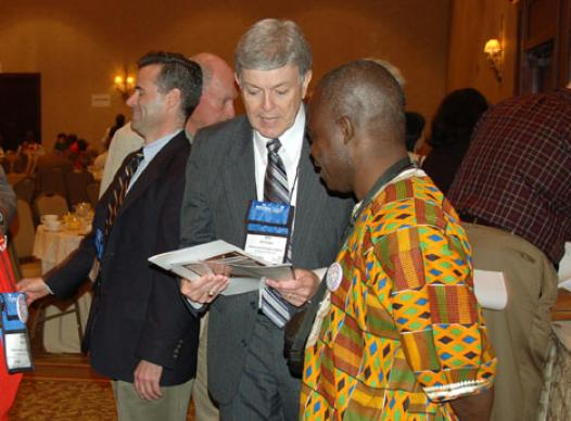 The Rev. James Heidinger, president and publisher of Good News, speaks with the Rev. Jerry Kulah, a Liberian delegate, during an April 25 Renewal and Reform Coalition breakfast briefing at the Fort Worth Hilton Hotel.