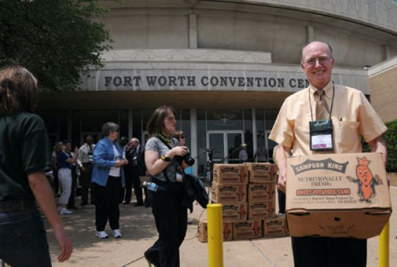 United Methodist Bishop Kenneth Carder helps load donated sweet potatoes for distribution to area missions serving the hungry in Fort Worth, Texas.