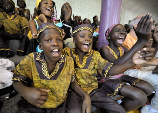 Members of a Ugandan children's choir cheer during a fundraising basketball game. The children (from left) are Ronald Kabubi, 10; Tonny Kyembe, 8; and Winnifred Acibo, 11.