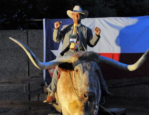 Solomon Christian gets his photo made atop a long-horned steer at