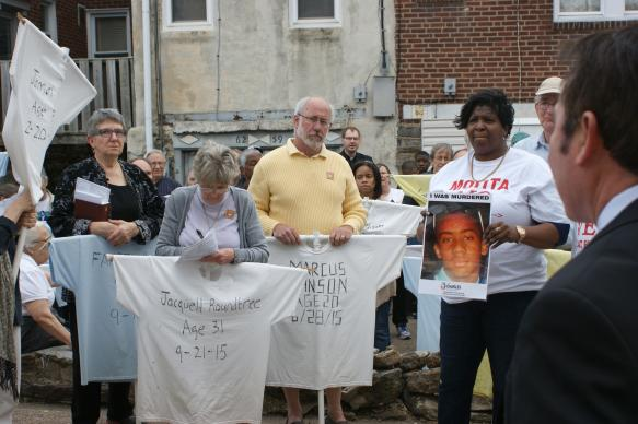 Participants of many faiths pick up shirts of the Memorial to the Lost in preparation for carrying them in the walk on Good Friday, March 25 in Philadelphia organized by Heeding God's Call to End Gun Violence.