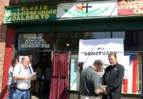 The Rev. Walter Coleman (right), pastor of Adalberto United Methodist Church, is interviewed by news reporters outside the Chicago church's storefront entrance in 2006. Church member Flor Crisóstomo from Mexico has taken refuge in Adalberto, which provided sanctuary to another member last year. A UMNS file photo by Linda S. Rhodes.