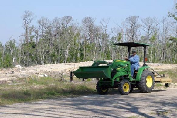 Abraham Carey drives a tractor across the grounds of Gulfside Assembly. More than 20 months after Hurricane Katrina destroyed the historic United Methodist facility, debris still litters the area. A UMNS photo by Kathy L. Gilbert.