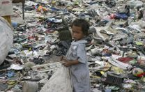 A young girl is surrounded by trash at the dump nicknamed Smokey Mountain in Manila, Philippines. The city's poorest people live in the dump and make their living looking for goods to recycle.