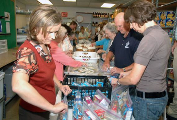 Holley Williams (left) and Ronnie Crowley pack after-school snacks for needy children as part of the Snack Sacks ministry of Arborlawn United Methodist Church in Fort Worth, Texas. UMNS photos by John Gordon.