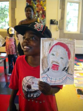 A child at Mom's Place shows off his painting created during the after-school art program at Cass Community United Methodist Church.
