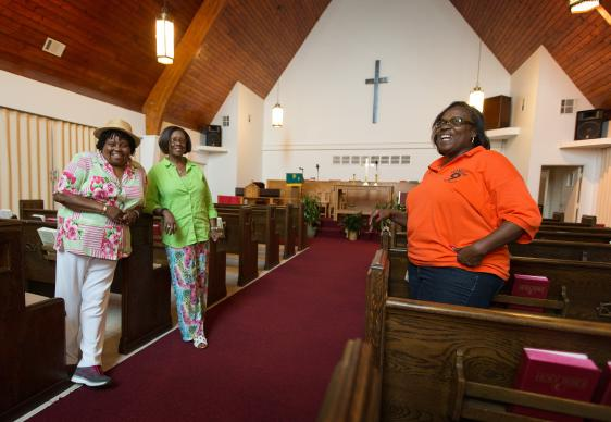 Church members (from left) Burnetta D. Fauria, Angelique White-Williams and Andrea Sanchez-Reese show the restored sanctuary at Hartzell United Methodist Church in New Orleans' Lower 9th Ward. Among the items dedicated last year were new imprinted hymnals from Cokesbury Cares.