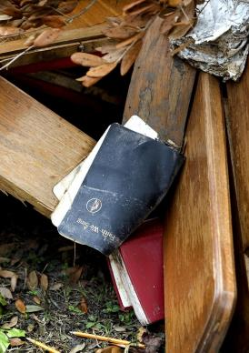 Muddy, waterlogged lie hymnals among the ruined furnishings of Hartzell Mt. Zion United Methodist Church in Slidell, Louisiana., where the sanctuary was flooded by storm surge from Hurricane Katrina in August 2005.