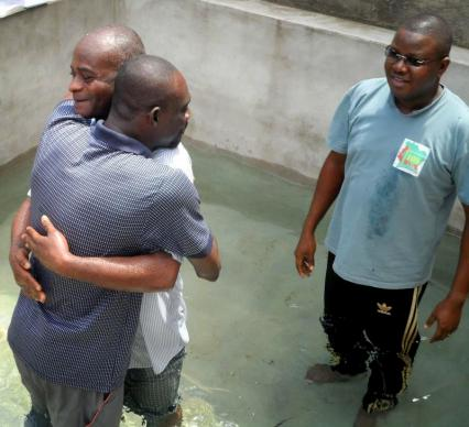 The Rev. Sory Abraham Dosso (right) prepares to join the celebration following the baptism of one of his congregants.