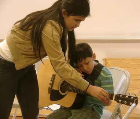 Coral Romero, youth band member and guitar teacher at Christ's Foundry United Methodist Church, helps Guitars with Grace student Kevin Landlin with his fingering.