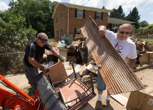 The Rev. Ricky Duncan (right) of Johnson Memorial United Methodist Church and parishioner Randall Lester help remove flood debris from the home of a neighbor in Alderson, W. Va.