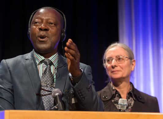 Stanislas Kassongo addresses the Pre-General Conference Briefing with the assistance of translator Isabelle Berger.