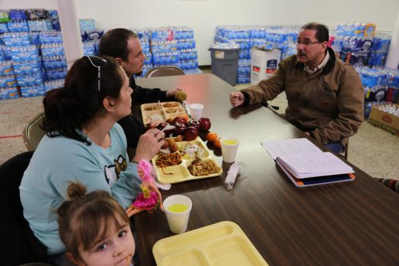 Pete Plum (right) meets with a family at Lincoln Park United Methodist Church in Flint to give them a resource kit and urge them to test their water at home. The church provides bottled water and filtering units. Members also provide a daily fellowship luncheon for their neighbors.