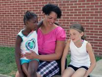 Director Celes Sheffield visits with two of the youngsters served by Ebenezer Community Outreach, a